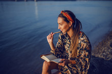 Portrait Of Pensive Attractive Caucasian Brunette In Floral Dress And With Headband Sitting On Rock On Shore Next To River And Writing Diary.