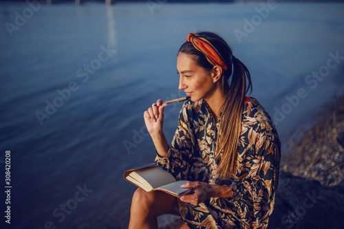 Portrait of pensive attractive caucasian brunette in floral dress and with headband sitting on rock on shore next to river and writing diary Fototapete