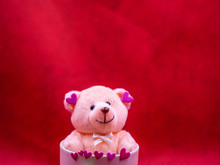Closeup Of Smiling Teddy Bear Doll With Pink Heart Shape Sticker And White Coffee Cup On Vivid, Vibrant Red Background For Happiness, Cheerful, Love, Valentine, Positive Thinking Concepts And Ideas.