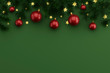 Flat composition with Christmas decor from the branches of the Christmas tree and Christmas balls on a green background, place for text