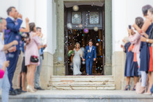Newlyweds Exiting The Church After The Wedding Ceremony, Family And Friends Celebrating Their Love With The Shower Of Soap Bubbles, Custom Undermining Traditional Rice Bath.