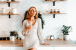 glamorous girl in a shining dress in the kitchen. cheerful woman with a glass of wine. lonely lady greets St. Valentine's Day