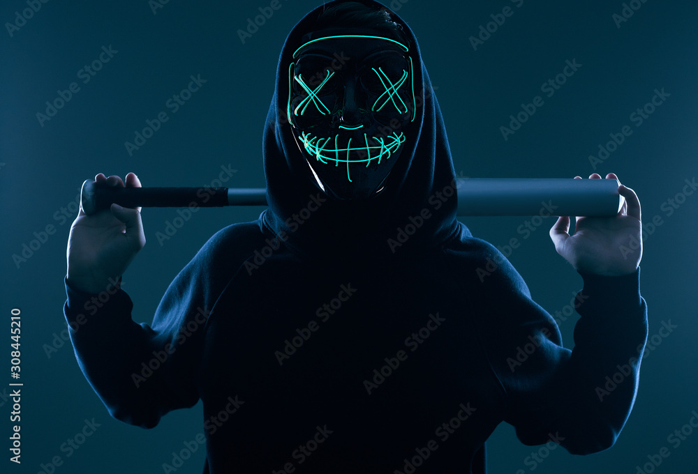 Fototapeta Anonymous criminal man with baseball bat in a black hoodie and neon mask
