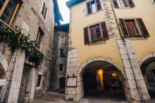 Medieval Buildings At The Center Of Old Annecy, France. Photography Of A Small European Courtyard From Old Buildings Of Various Architectural Styles With An Arch On The Ground Floor.