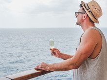 Handsome Man Holding A Beautiful Glass On The Open Deck Of A Cruise Liner Against The Backdrop Of Blue Sea Waves. Side View, Close-up. Concept Of Leisure And Travel