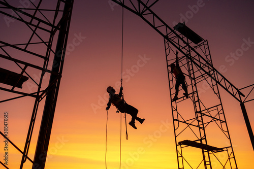 Male working abseiling on a construction site silhouette worker Canvas Print