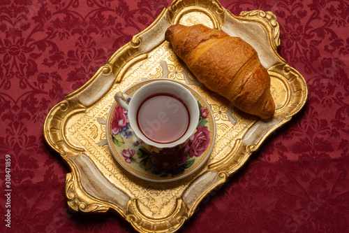 Fotografie, Tablou Top view of old-fashioned vintage floral cup of tea and croissant on Florentine