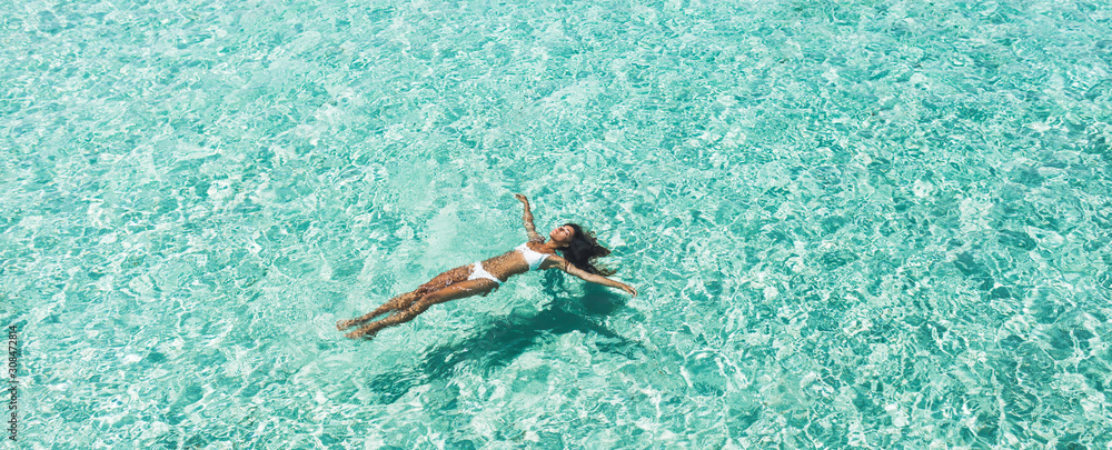 Fototapeta Woman in white bikini lying on transparent turquoise water surface on beach. Travel and vacations concept. Tropical background with empty space