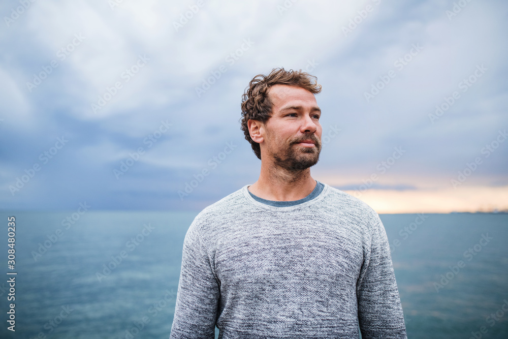 Fototapeta Mature man standing outdoors on beach at dusk.