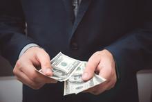 Man Counts Dollar Banknotes