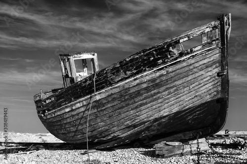Fotografija abandoned old fishing boat on the beach