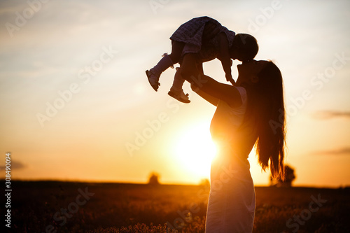 A mother lifts a toddler child in the air above a picturesque sunset sky. A woman and a little girl in a field of lavender flowers. Copy space