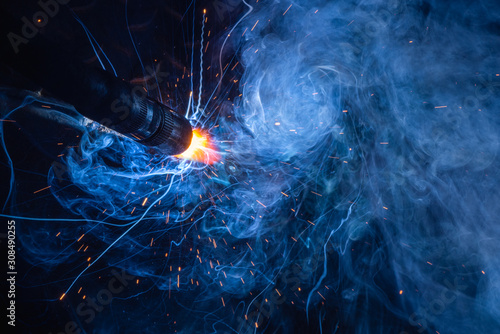 Closeup welding torch of Flux Core Welding process, FCAW,.Industrial welder welding fabricated construction in factory.