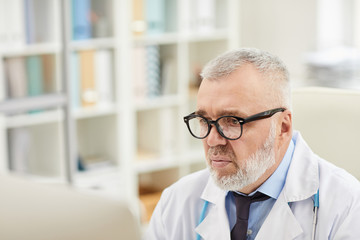 Mature doctor in eyeglasses looking at computer monitor and concentrating on his work
