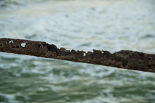 Old Rusty Pipe Handrail Fencing Breakwater On The Background Of The Sea