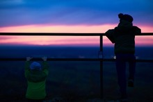 Picture Of Two Kids Watching The Beautiful Sunset Near The Fences Surrounded By Greenery