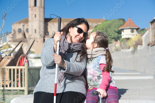 Blind mother with a white cane and her daughter talking sitting on a bench in the park and smiling Fototapet