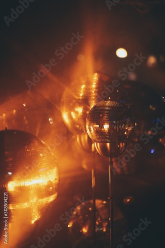 Closeup of mini disco balls under red and orange lights with a blurry background - 308504221
