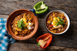 """Texmex dish called """"Chili con carne"""" with cheese and sour cream on wooden background"""