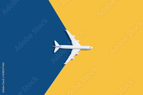 Flat lay design of travel concept with plane on blue and yellow background with Canvas Print