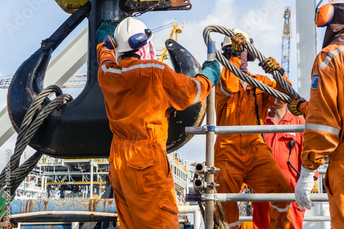 Fotografering Offshore workers installing a heavy lifting sling onto a crane hook on board a c