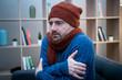 Leinwandbild Motiv Man feeling very cold at home with warm clothes