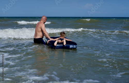 Fotografie, Obraz father with son on an airbed at sea