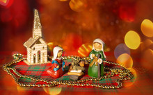 Wooden Nativity With Red Bokeh And Shiny Chapel