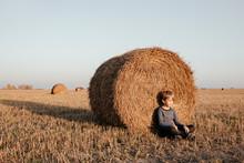 Boy Leaning On Hay Bale In Field