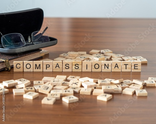 Obraz na plátne compassionate the word or concept represented by wooden letter tiles
