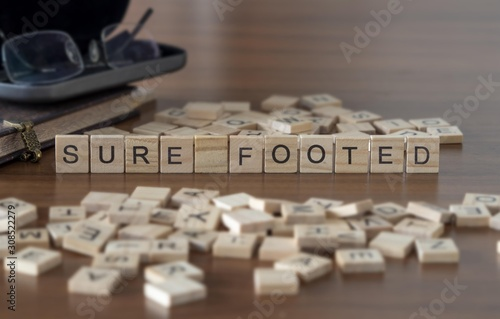 Photo sure footed the word or concept represented by wooden letter tiles