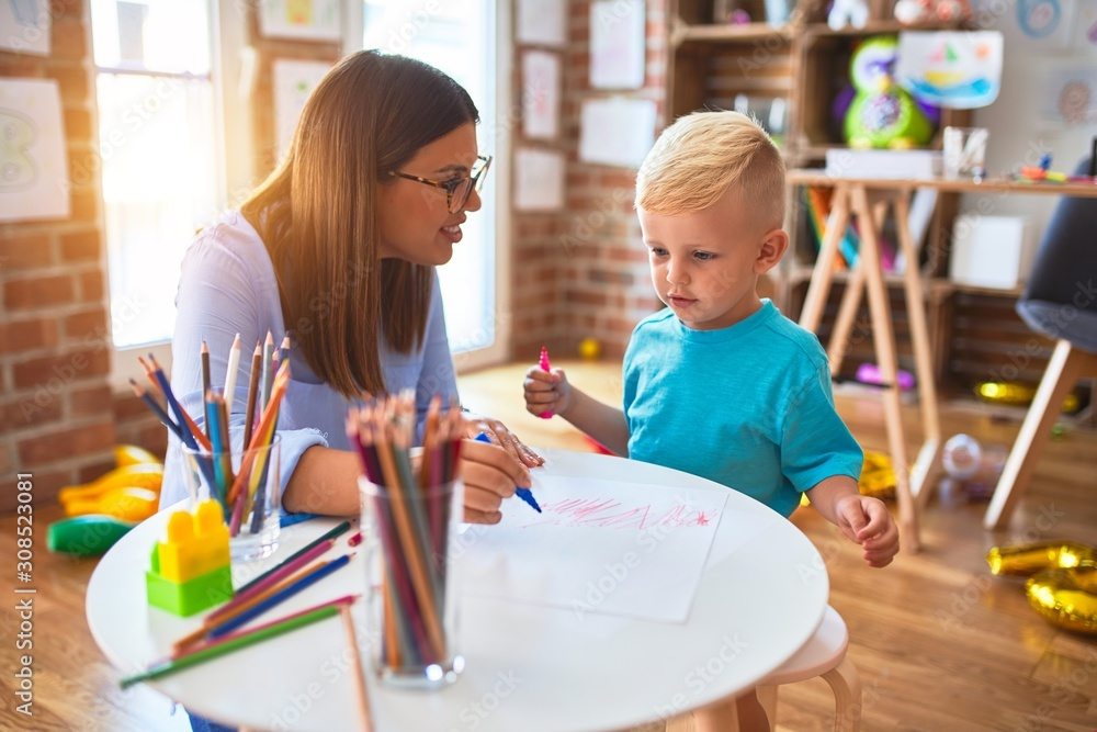 Young caucasian child playing at playschool with teacher. Mother and son at playroom drawing a draw with color pencils