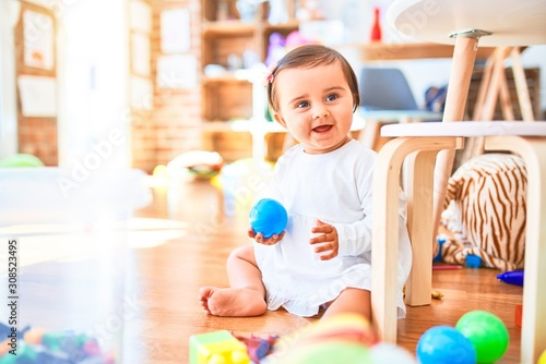 Fototapeta Beautiful infant happy at kindergarten around colorful toys