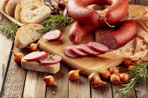 obraz dibond On a old wooden table sausage with bread, rosemary, onion and pepper.