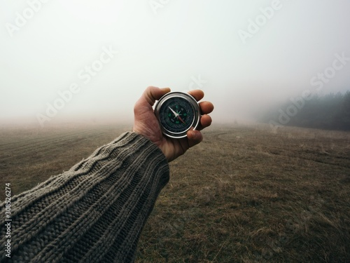 Obraz na plátne Man explorer searching direction with compass in the foggy field