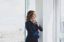 Mature Businesswoman Looking Out Of Window In Office