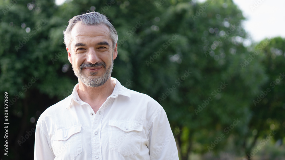Fototapeta Portrait shot of happy, retirement, attractive bearded middle-aged man smiling with a confident look toward the camera at a blur park background with copy space in natural sunlight.