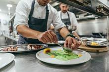 Chef Garnishing Plate With Food