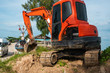 Small orange excavator on a ground against blue sky and sea for a works on construction site. Small tracked excavator standing on a ground with a blue sea on background. Heavy industry.