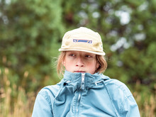 Portrait Of Teen Boy Looking Off Frame With Hat And Wind Breaker