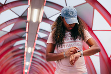 Black Woman Checking Smart Watch With Creative Background