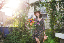 Happy Woman Holding Flowers In...