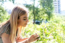 Young Blonde Woman Eyes Closed Smelling Flowers In A Park