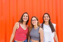 Three Young Happy Teenage Girls Have Fun Against Orange Wall