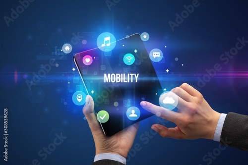 Cuadros en Lienzo  Businessman holding a foldable smartphone with MOBILITY inscription, social medi