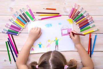 Dijete s obitelji crta rođendansku čestitku. Crtež koji je dijete izradilo šarenim flomasterima i olovkama. Sretna obitelj. Dječji crtež