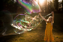 9 Year Old Girl Making Giant Bubble In Summer Light
