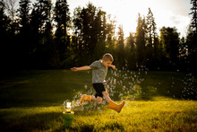 5 Year Old Boy Jumping Through Bubbles In Golden Light