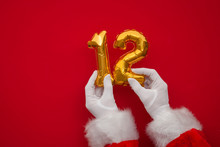 12 Days Of Christmas. Santa Hands Holding 12th Day Balloon On Red Background