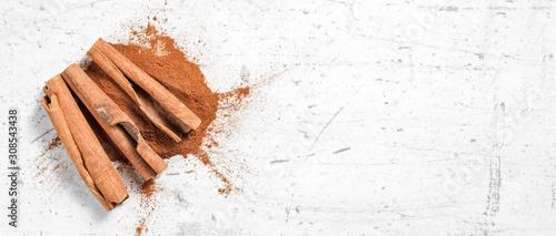 Photo Cinnamon bark sticks and ground powder on white stone like board, wide banner -
